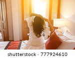 Woman Sitting Back On The Bed ...