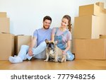 Stock photo mortgage people and real estate concept happy couple with boxes and french bulldog dog moving to 777948256
