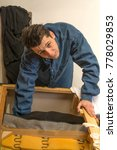 Small photo of upholsterer padding a sofa with open framing in the upholsterer shop