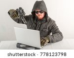 Small photo of An evil hacker with a gun, red hair, a beard and a mustache. Penetration into the home, hacking laptop, emotion, cinema, sun glasses