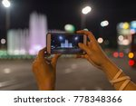 Young woman takes photos using smart mobile cell phone camera of a dancing fountain in Belgrade - stock photo