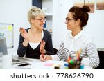 Small photo of Close up of two smiling stylish business middle aged women working and having a conversation while sitting in the office one next to another.