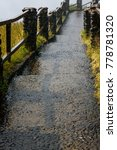 Small photo of Wet aggregate concrete path of Victoria Falls with rock posts and wood fence rails