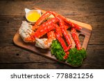 Cooked Organic Alaskan King Crab Legs with Butter and lemons,Alaskan King Crab on vintage wooden background.