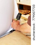Small photo of Upholsterer removing old staples from the chair using a rubber hammer