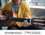 Small photo of Close up of hand of cheerful young man playing guitar and smiling. Focus on his fingers making accord on strings