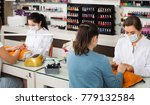 Small photo of professional nail technicians performing manicure procedure behind the workplace in beauty salon