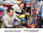 Stock photo smiling young boyfriend helping happy girl to choose bowl in pet store focus on guy 779182840