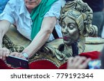 Small photo of Bucharest, Romania - May 29, 2014: A man takes selfie picture with an actress acting as Baroque couch ornament throughout The Sofa show during B-Fit International Street Theater Festival.