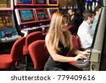 Pretty young woman having a good time playing slots in a casino. With some copy space - stock photo
