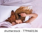 Stock photo beautiful girl is sleeping under a blanket on a pillow with her favorite dog in bed image 779460136