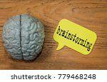 Small photo of motivation empty green sticker near human brain lie on wooden table. gray brain. inspirational label with textured brain and Brain Storm idea