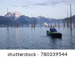 Small photo of Adventurous girl is kayaking on an inflatable kayak on a beautiful lake with mountains in the background