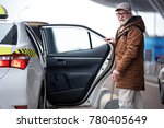 Small photo of Portrait of positive bearded old man in glasses is going to sit into the car. He is opening door of taxi and looking at camera with smile. Copy space in the right side