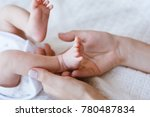 mother holds the legs of her... | Shutterstock . vector #780487834