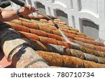 a workman cleaning a tiles roof ... | Shutterstock . vector #780710734