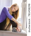 Small photo of People and solitude concept. Alone sad young woman long hair teen girl sitting on window sill lost in thought