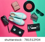 Small photo of Sneakers, vinyl records, audio cassettes, video cassettes, plastic vintage camera, purse are laid out on a neon colored surface. Entertainment 90s. Top view. Flat lay.