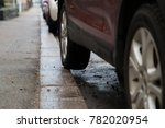 Small photo of Bad car parking with part of the rear tyre on the pavement