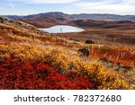 Autumn greenlandic orange tundra landscape with lakes and mountains in the background, Kangerlussuaq, Greenland