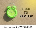 Small photo of alarm clock with text time to review over sand background