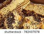 Small photo of Honey in honeycombs, large pieces. Hexahedral cells covered with light beeswax. Natural product, health benefits. Lateral solar illumination.