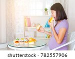 over eating pregnant woman | Shutterstock . vector #782557906