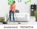 Young Woman Hoovering Carpet A...