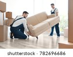 Delivery Men Moving Sofa In...