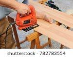 carpenter cutting a wooden...