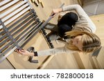 young woman assembling bed in... | Shutterstock . vector #782800018
