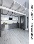 Small photo of Wooden mezzanine over modern kitchen with bright wood floor