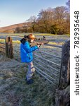 Small photo of Teenage boy firing an air rifle on farmland on a cold, frosty day.