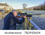 Man and teenage boy firing an air rifle on farmland on a cold, frosty day. - stock photo