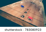 Small photo of Vintage shuffle board game with red and blue disc on wooden shuffle table. Shuffleboard table game with selective focus.