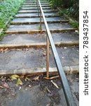 Small photo of stairs with central iron handrail in a park