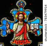 Small photo of PRAGUE, CZECH REPUBLIC - APRIL 2, 2016: Stained Glass window in St. Vitus Cathedral, Prague, depicting Jesus Christ holding the bible with Greek Letters Alpha and Omega.