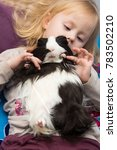 Small photo of A little cute little girl is playing with a pet. Children and rodents