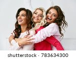 Small photo of Female Friends Having Fun Together At Home Party. Beautiful Smiling Girls In Colorful Fashionable Pajamas Hugging And Enjoying Home Party In Light Interior. Women Friendship. High Quality Image