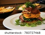 Small photo of Corn fritter with bacon, halloumi and spinach in white plate serve on wood table. Fresh cook corn fritter on wood table with cafe background
