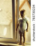 Small photo of Cute baby boy kid child with blond hair in striped romper stays on window sill at home