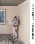 Small photo of A worker plastered the interior walls with a plaster pump machine on the construction of a private house. Concept; construction site