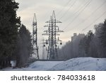 Small photo of electricity pylons of air power line in a snowy forest in the suburbs