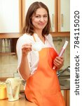 Small photo of Relax and rest in kitchen. Middle aged woman chef housekeeper holding cookbook with cup of tea coffee. Housewife resting at home.
