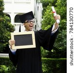 Small photo of Graduate student with gown ,cap and certificate in hand and holding board with green background. Happy young teenage man with gown and holding board. Education concept. New graduate student .
