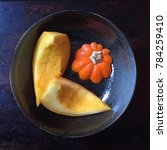 Small photo of three slices of raw acorn squash in a gray glazed ceramic bowl on a dark background