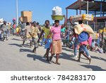 Small photo of Dajaban / Haiti - July 15, 2011: Haitian woman carries a bucket of goods on her head while men carry a poultry crate and sack of grains at Haitian / Dominican Republic border market.