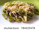 Small photo of Egg alimentary pasta with spinach on a plate, food background