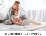 Small photo of Full length of cheerful woman relaxing with little child on the floor and showing her laptop