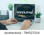 Small photo of Installing weekend please wait note concept / Hands on laptop in office